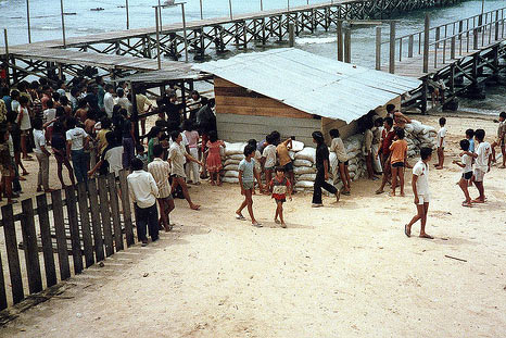 About Sri Avinash Do - The long jetty and entrance to Pulau Bidong, Malaysia, the Vietnamese refugee camp where Sri Avinash stayed. The photo shows the weekly food ration being distributed.